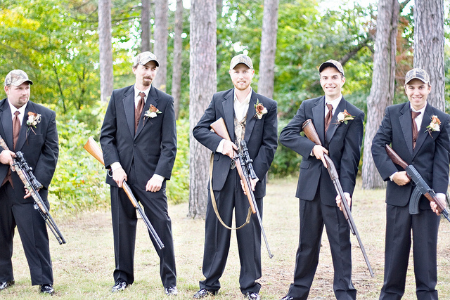 A shot of the groomsmen posing with their guns.