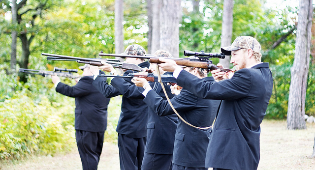 A shot of the groomsmen with guns after the wedding ceremony.